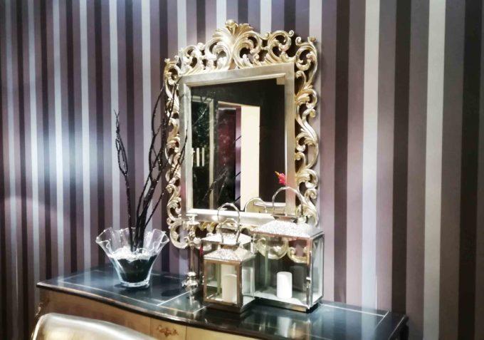 Specchio con cornice in legno e finitura argento anticata.